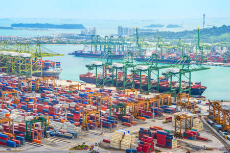 Aerial view of cargo ships in Singapore industrial port harbor by pier with freight cranes and goods containers, seacsape at background Foto de archivo
