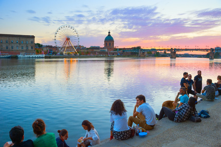 TOULOUSE, FRANCE - AUGUST 13, 2017: People resting at the embankment of Garone river in Toulouse. Toulouse is the capital of the region of Occitanie