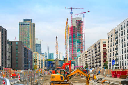 Excavator, cranes and construction equipment at construction site in downtown at street with buildings and skyscaraprers of modern architecture, Frankfurt am Main, Germany 版權商用圖片