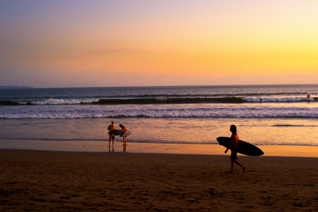 Surfers on beach at scenic sunset, Bali, Indonesia