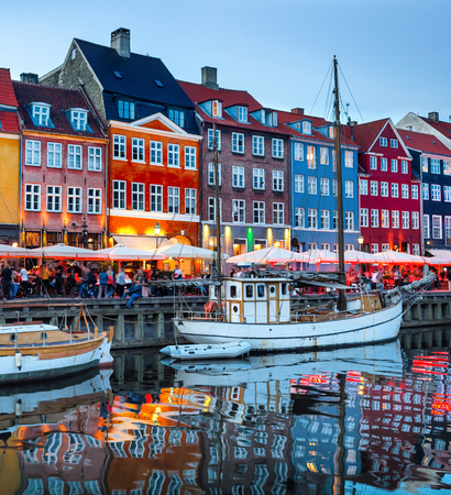 Sailboats moored by Nyhavn promenade illuminated at the evening, Copenhagen old town cityscape, Denmark