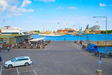 COPENHAGEN, DENMARK - JUNE 14, 2018: Tourists in outdoor cafe at Copenhagen harbor, bicycles parking on pier, ship passing by urban city skyline