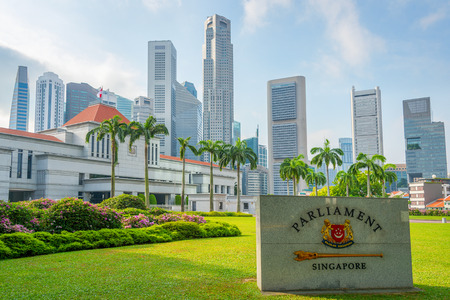 Singapore Parliament building, marble plate on green grass lawn, city skyline in background Редакционное