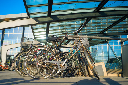 Closeup of bicycles on parking by Kastrup International airport under glass canopy in sunshine day, Copenhagen, Denmark