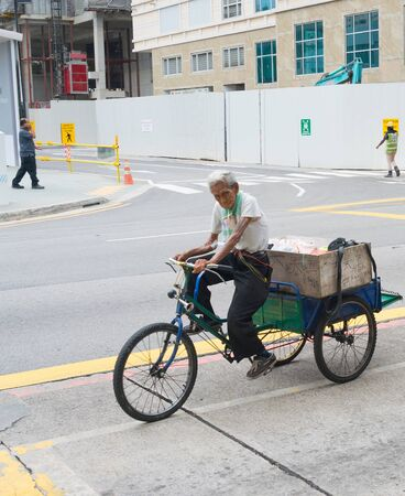 SINGAPORE - FEBRUARY 18, 2017: Man riding a tricycle on the road in Singapore. Singapore is the major financial center in Asia