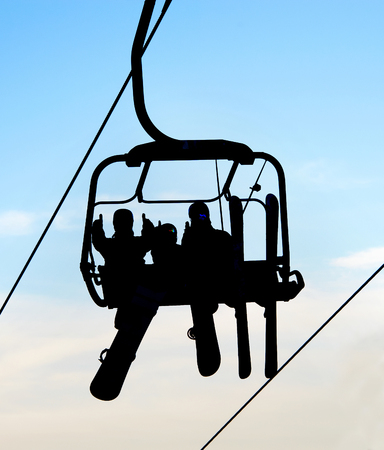 Silhouettes of people with skis and snowboards on chairlift against sky, Bukovel, Ukraine
