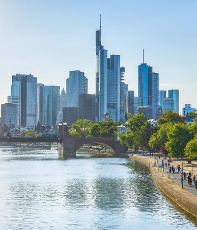 People walking by green Frankfurt embankment in evening sunlight, city skyline at background. 免版税图像