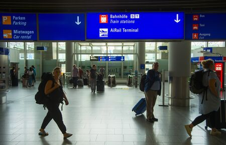 FRANKFURT AM MAIN, GERMANY - AUGUST 29, 2018: People with luggage exiting Frankfurt airport, Info board with direction signs above, Frankfurt am Main, Germany