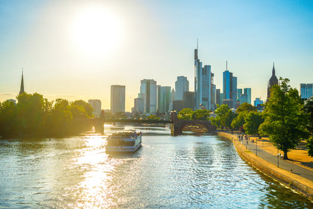 Sunshine evening, touristic boat at Main river, Frankfurt skyline of modern architecture and people walking by embankment, Germany
