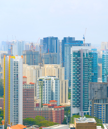 Density architecture, construction activity in Singapore. Cranes and modern buildings
