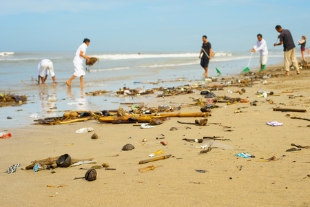 Groep mensen die het strand opruimen van het afval en het plastic afval.
