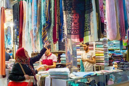 TEHRAN, IRAN - MAY 22, 2017: Woman looking at silk fabrics, textiles and colorful shawls at Grand Bazaar - main market in Tehran