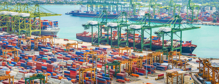 Aerial panorama of cargo ships in Singapore industrial port harbor by pier with freight cranes and goods containers, seacsape at background Stock Photo