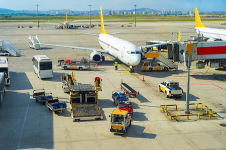 Passengers leaving plane, service buses, gangway, luggage transporters at runway in bright sunshine, Istanbul airport, Turkey Reklamní fotografie