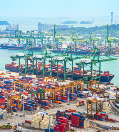 Aerial view of cargo ships in Singapore industrial port harbor by pier with freight cranes and goods containers, seacsape at background