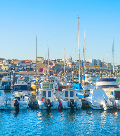 White yachts and motor boats moored by pier in marina, Peniche, Portugal