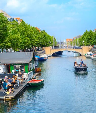 COPENHAGEN, DENMARK - JUNE 14, 2018: People in a riding boat and eating at waterfront restaurant  in Copenahgen. Copenhageni s the capital of Denmark Editorial