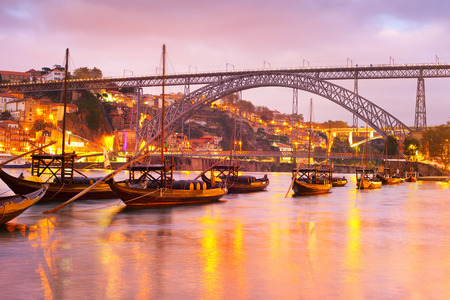 Scenic sunset over Douro river with traditional wine boats, illuminated Porto skyline and Dom Luis I bridge in background, Portugal