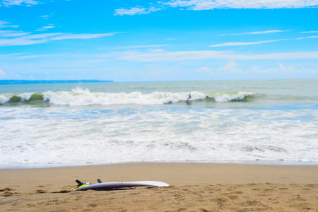 Surfboard on sandy beach, surfer riding on waves in background, Bali, Indonesia