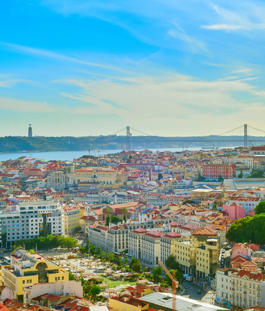 Skyline of Lisbon old town, 25th April Bridge and Christ the King statue on the Tagus river
