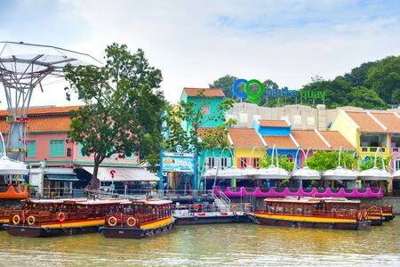 SINGAPORE - FEBRUARY 15, 2017: Colorful houses of Clarke Quay district by the river with traditional boats