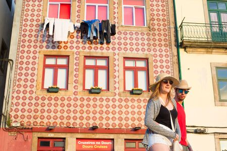 PORTO, PORTUGAL - JUNE 2, 2017: Couple of tourists in sunglasses walking by old town street of Porto, traditional house wall decorated with red tiles, clotheslines by window in background