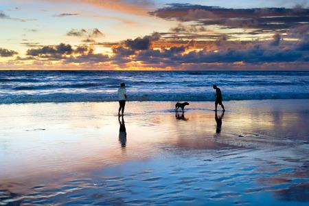 Pareja jugando en la playa con perro, pintoresco paisaje marino al atardecer en el fondo, Bali, Indonesia Foto de archivo