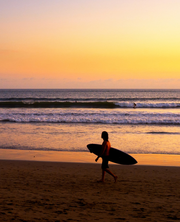 Surfer on beach at scenic sunset, Bali, Indonesia