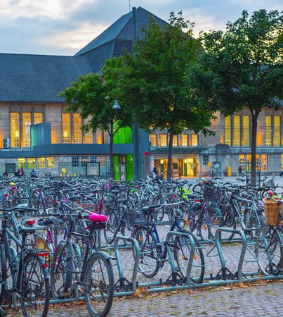 Big bicycles parking by train station in susnet dusk, Dortmund, Germany