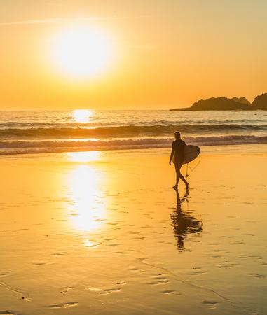 Silhouet van surfer wandelen naar de oceaan door zandstrand, schilderachtige gouden zonsondergang over zeegezicht, Sagres, Algarve, Portugal Stockfoto