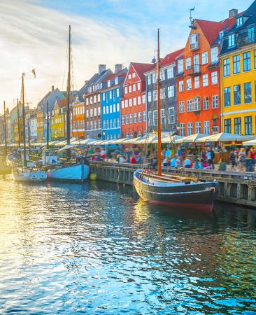 Nyhavn view with boats by embankmentat sunset, people walking and sitting at restaurants, Copenhagen, Denmark