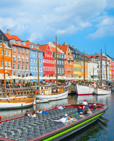 Tour boat sailing by canal with old sailboats in Nyhavn harbor, peopel walking at sunny embankment and sitting in cafes and restaurants, Copenhagen, Denmark