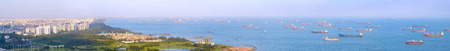 Panoramic view of Singapore harbor with many cargo ships at sunset. Singapore Imagens