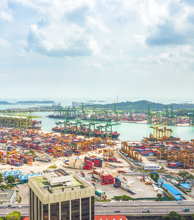 Aerial view of Singapore cargo shipping port, transportational containers, freight cranes in urban city area, seascape in background Imagens