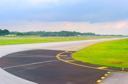 Empty runway at Changi airport in Singapore, departuring plane in the background Stock Photo