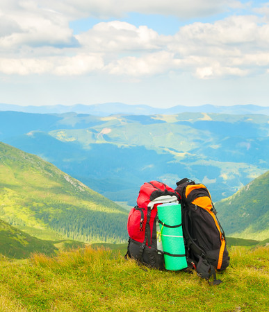 Two colorful hikers backpacks on green slope, scenic Carpathian mountains landscape in background, Ukraine