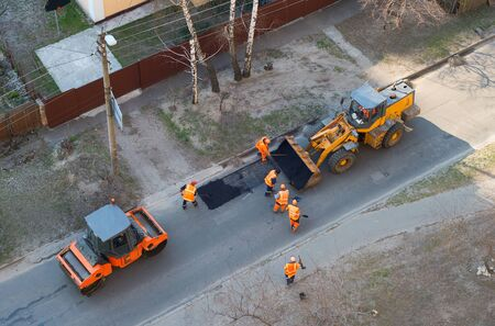 Workers, excavator, roller compactor repair road, top view, Kiev, Ukraine
