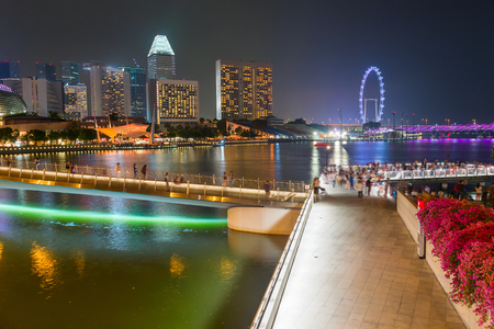 Tourists walking by Singapore embankment, illuminated Flyer, city skyline with modern architecture in background Editorial