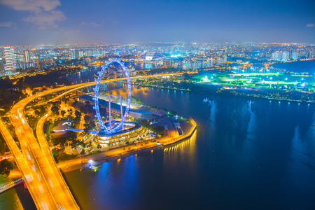 Aerial view of illuminated Singapore metropolis at night, embankment with ferris wheel ad city highway