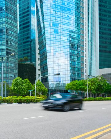 Rush hour in Singapore Downtown Core, car traffic on the road, modern architecture motion blur