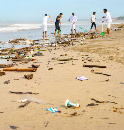 Group of people cleaning up the beach from the garbage and plastic waste. Stock Photo