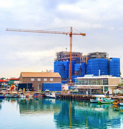 Construction site by Limassol waterfront, boats moored in marina with cafes and restaurants, Cyprus Stok Fotoğraf