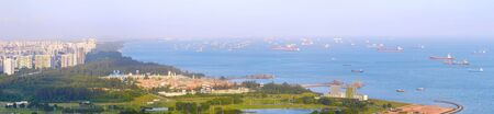 Panorama of Singapore harbor with many cargo ships at sunset. Singapore