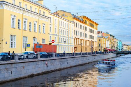 Downtown cityscape, Griboedova street with bridge over canal in sunset light, sightseeing tourists on cruise boat, Saint Petersburg, Russia
