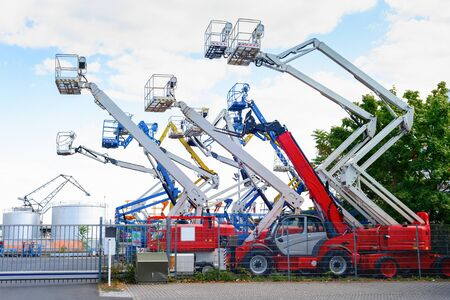 Colorful aerial platform cranes, machines and working equipment in industrial area, Frankfurt, Germany Stock Photo