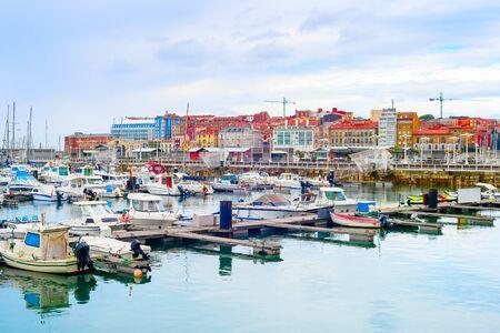 Citycsape nuvoloso con yacht e barche a motore ormeggiate da moli in marina, Gijon, Asturie, Spagna Archivio Fotografico