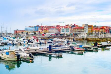 Overcast citycsape with yachts and motor boats moored by piers in marina, Gijon, Asturias, Spain Stock Photo
