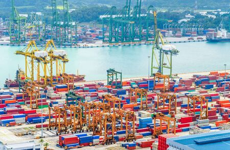 Aerial view of Singapore trade port, heavy equipment, cargo containers, freight cranes, docks and storages, harbor with ships and tankers Archivio Fotografico