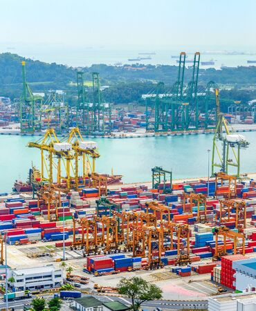 Aerial view of Singapore trade port, heavy equipment, cargo containers, freight cranes, docks and storages, harbor with ships and tankers