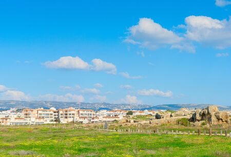 Viw of Paphos with green field and Paphos Mosaics in the foreground, Cyprus